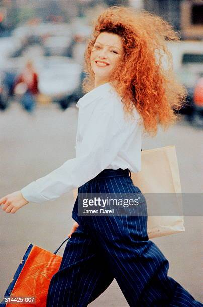 young woman carrying shopping bags, crossing road, smiling, close-up - commercial activity stock pictures, royalty-free photos & images