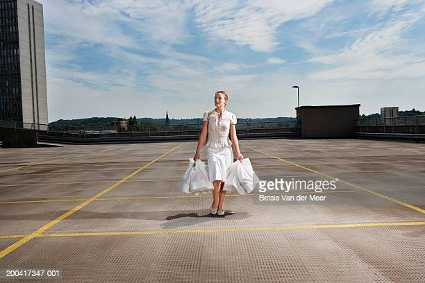 Young woman carrying shopping bags on rooftop carpark