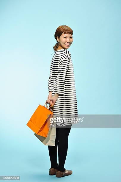Young woman carrying shopping bags , smiling