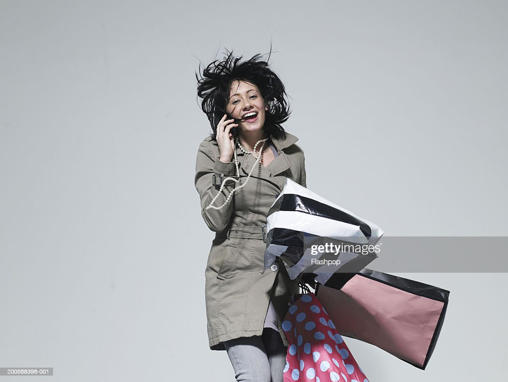 Young woman carrying shopping bags, using mobile phone : Stock-Foto