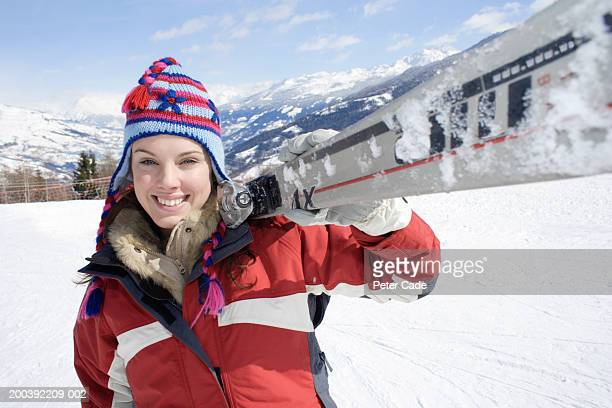 Young woman carrying skies on ski slope, portrait, close-up