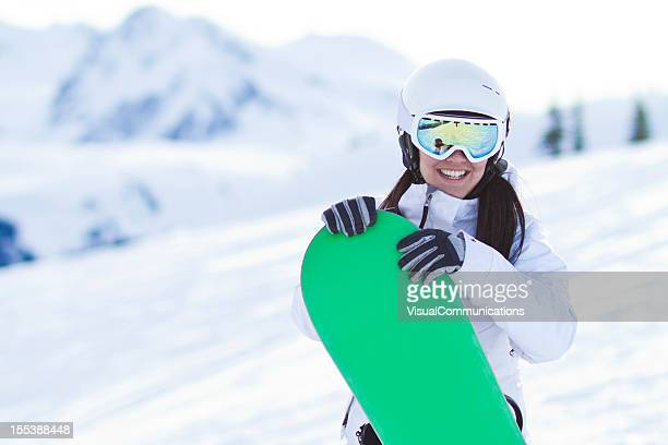 Young woman carrying snowboard.
