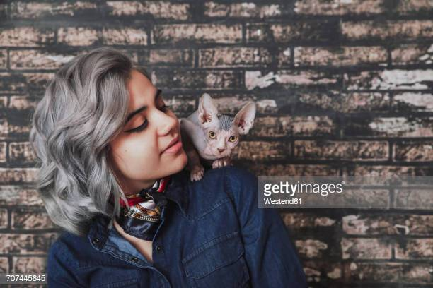 young woman carrying sphynx cat on shoulder - perching stock photos and pictures