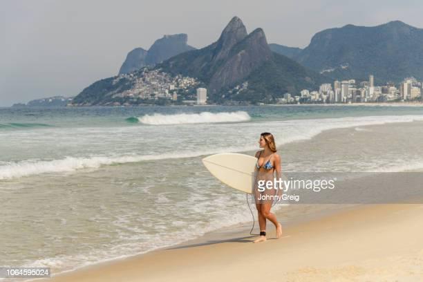 junge frau mit surfbrett, strand von ipanema - rio de janeiro stock-fotos und bilder