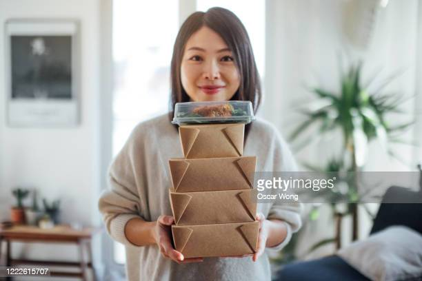 young woman carrying takeaway food boxes - take away food stock pictures, royalty-free photos & images