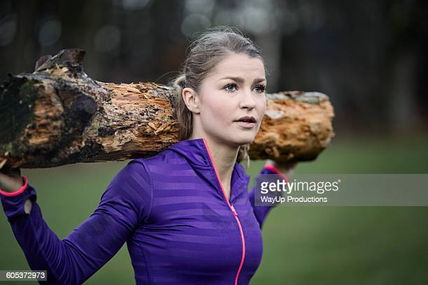 Young woman carrying tree branch on shoulder looking away