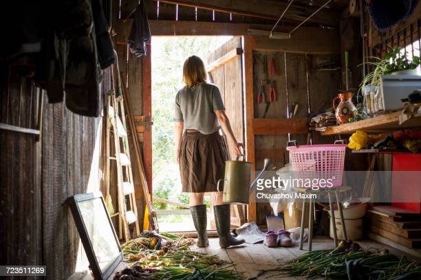 young woman carrying watering can looking out from garden shed - shed stock pictures, royalty-free photos & images