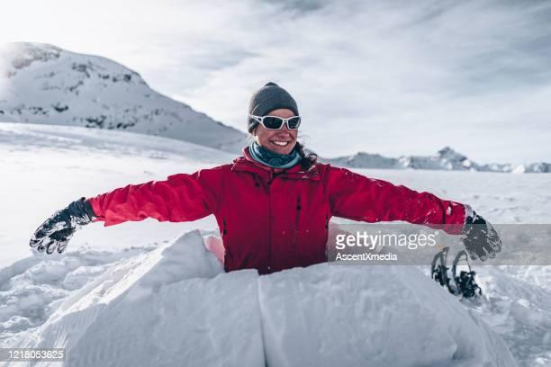junge frau schnitzt schnee, um iglu zu bauen - aktiver lebensstil stock-fotos und bilder