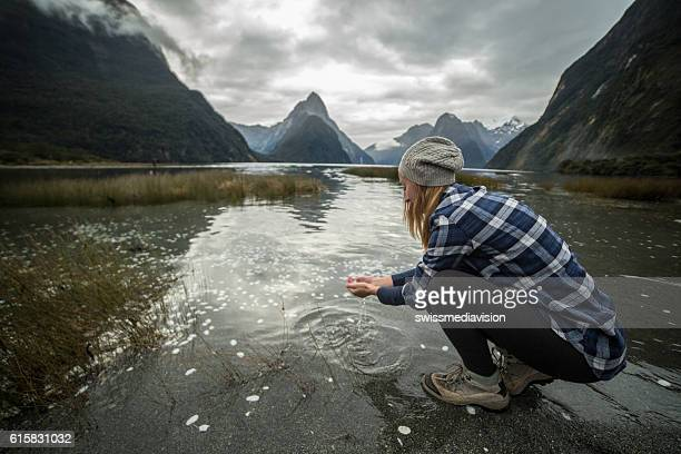 Young woman catches fresh water from lake, New Zealand