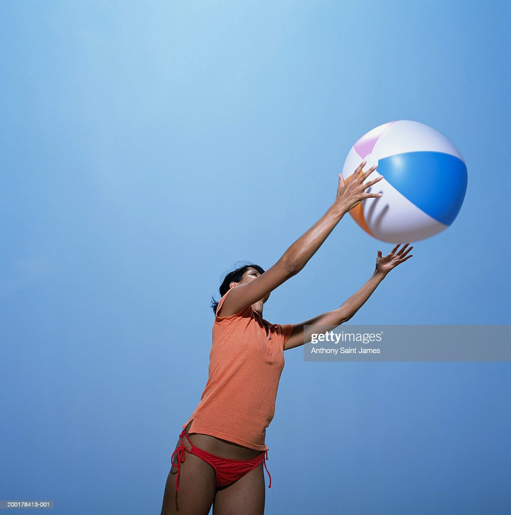 Young Woman Catching Beach Ball Side View High Res Stock
