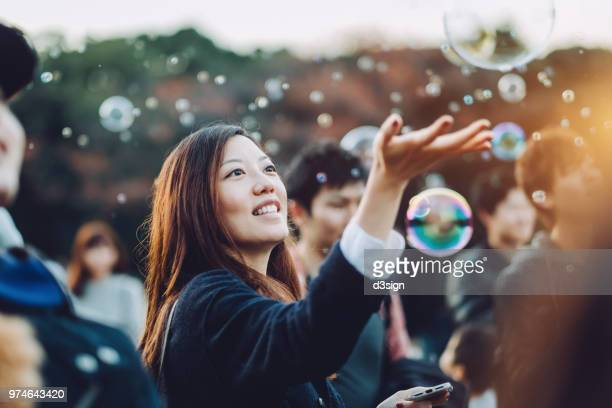 young woman catching bubbles joyfully in park - catching stock pictures, royalty-free photos & images
