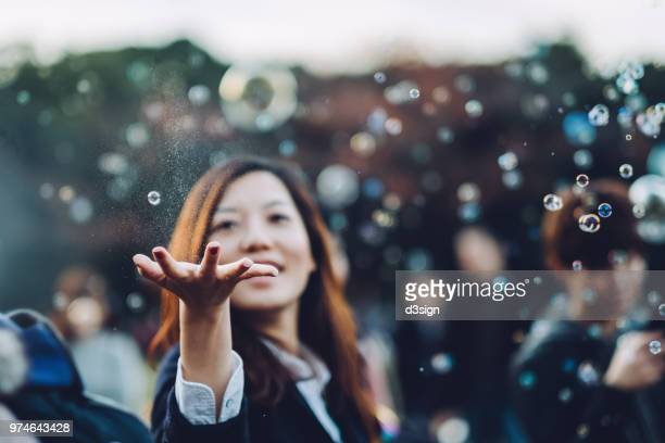 young woman catching bubbles joyfully in park - curiosity stock pictures, royalty-free photos & images