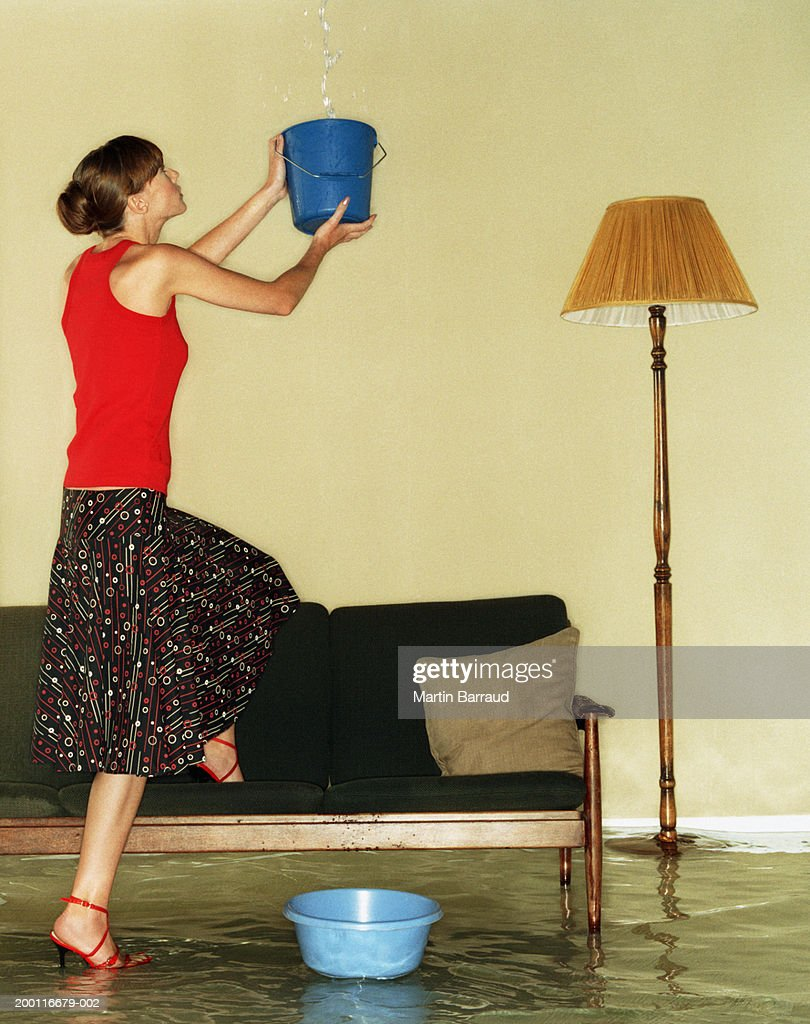 Young woman catching water in bucket in flooded room : Stock Photo