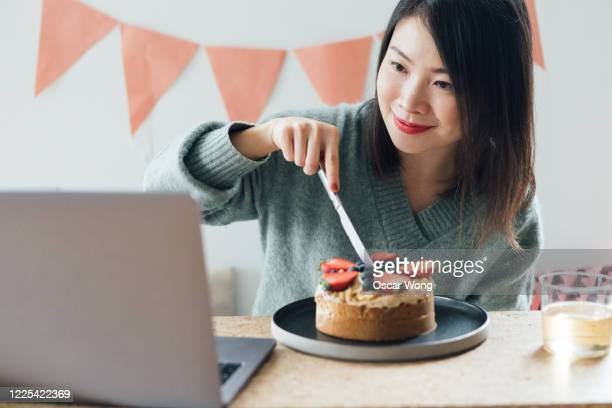 young woman celebrating birthday on a video call using laptop - cutting stock pictures, royalty-free photos & images