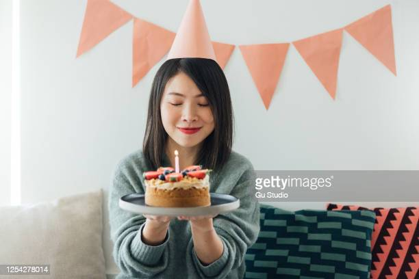 young woman celebrating birthday with a birthday cake - birthday cake stock pictures, royalty-free photos & images