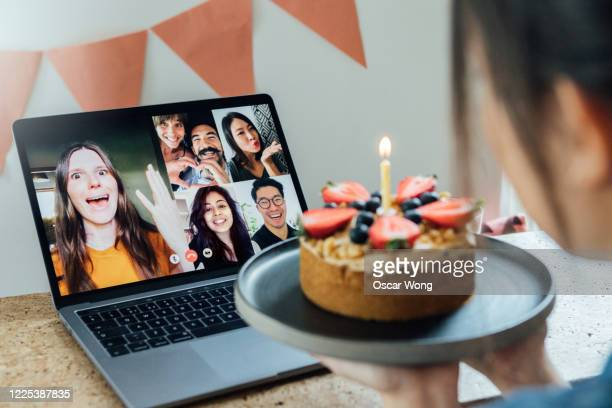 young woman celebrating birthday with friends on a video call using laptop - birthday stock pictures, royalty-free photos & images