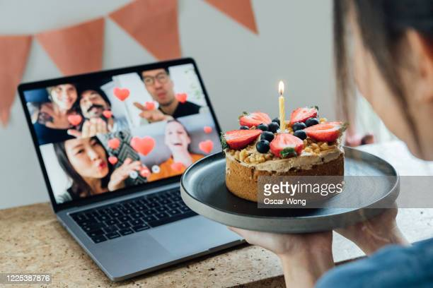 young woman celebrating birthday with friends on a video call using laptop - social distancing stock pictures, royalty-free photos & images