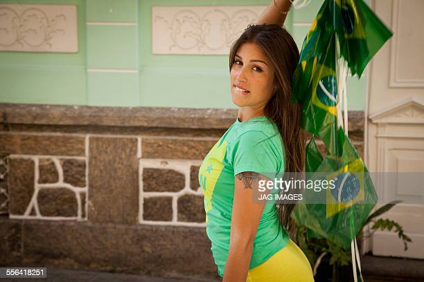 Young woman celebrating with Brazilian flags in the street, Rio de Janeiro, Brazil