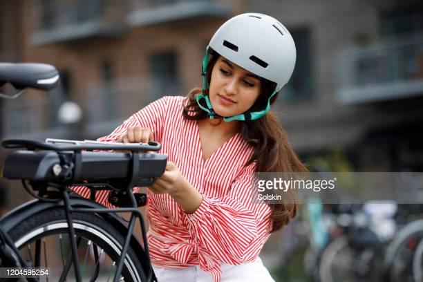 young woman changing battery pack on bicycle - casque de protection au sport photos et images de collection