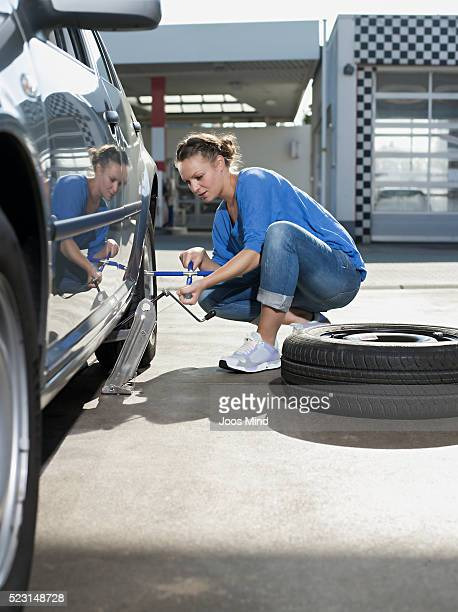young woman changing car tire at petrol station