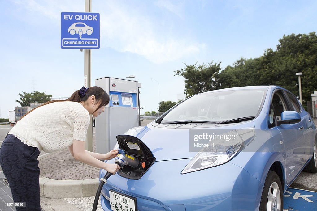 young woman charging Electric Car : Stock Photo