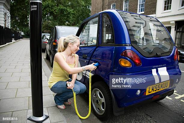 young woman charging electric car - electric vehicle charging station stock photos and pictures