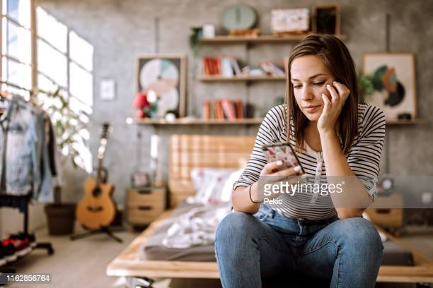 young woman chatting on mobile phone at home - online dating stock pictures, royalty-free photos & images