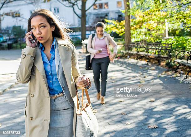 Young woman chatting on smartphone whilst walking through city park