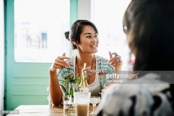 Young Woman Chatting With Friends In Cafe