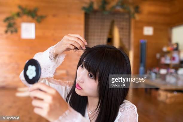 若い女性の髪をカフェで昼食後チェックイン