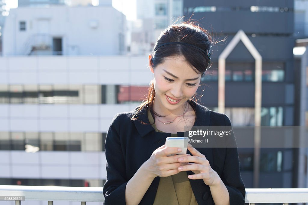 young woman checking a smartphone : ストックフォト