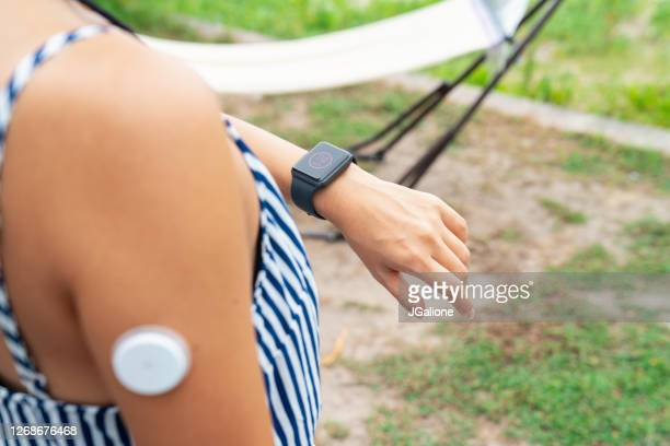 young woman checking a smartwatch to see her blood sugar level - wearable computer stock pictures, royalty-free photos & images