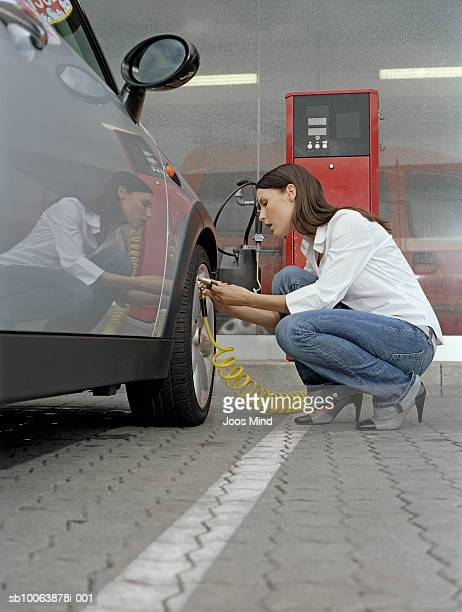 young woman checking air pressure of car tire, side view - inflating stock pictures, royalty-free photos & images