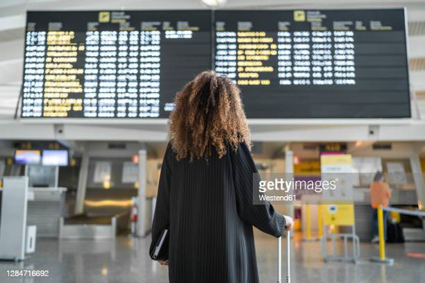 young woman checking arrival timing of flight on board standing at airport - anzeigetafel stock-fotos und bilder