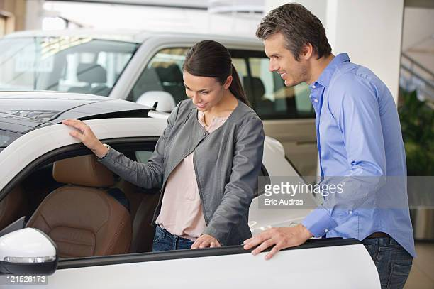 Young woman checking car from inside while man holding the door