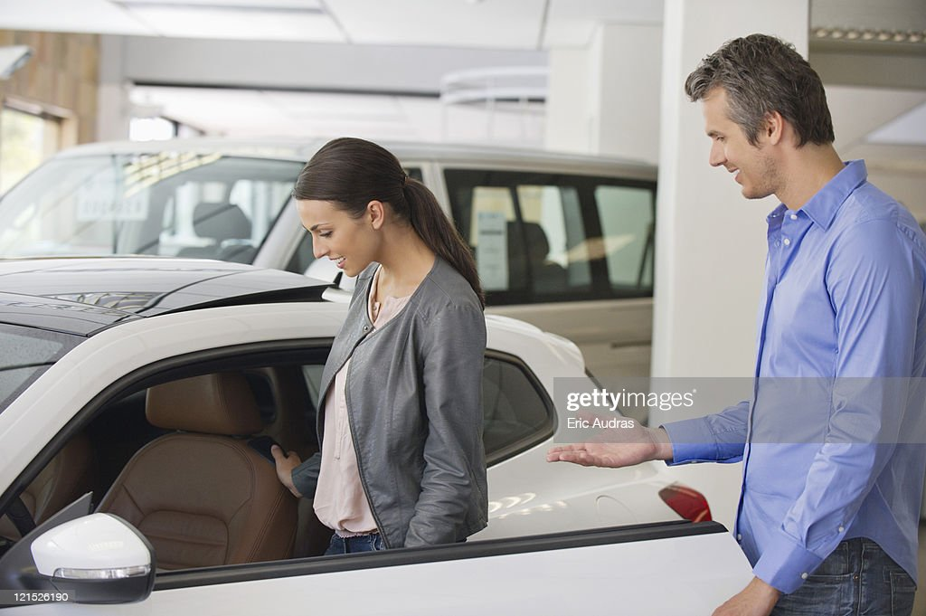 Young woman checking car from inside while man holding the door : Stock Photo