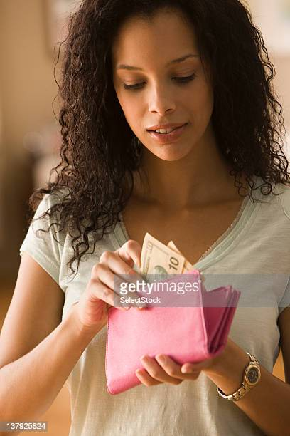 Young woman checking cash in wallet