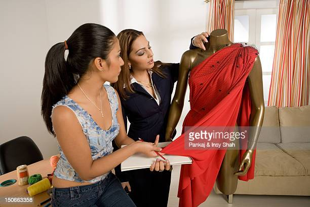 Young woman checking dressed mannequin, side view