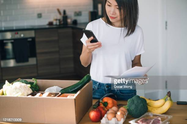 young woman checking food delivery with smartphone - meal stock pictures, royalty-free photos & images