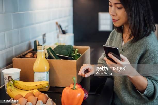 young woman checking food delivery with smartphone - flatten the curve stock pictures, royalty-free photos & images