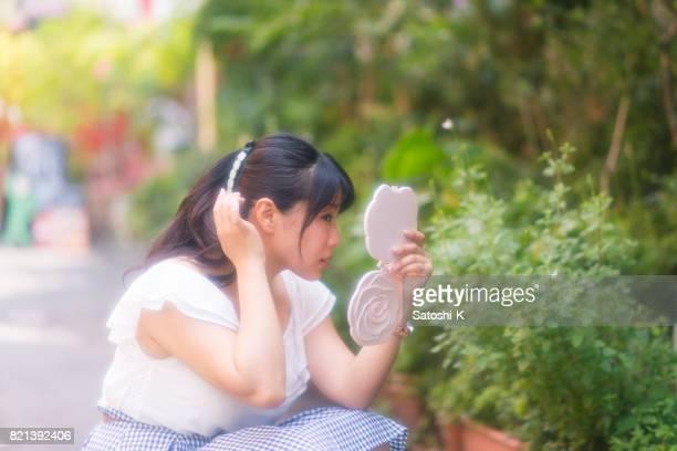 Junge Frau, die Haare mit Handspiegel in Stadt überprüfen