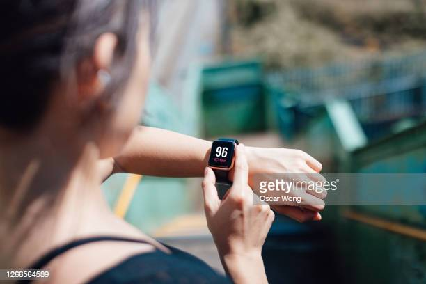 young woman checking heart rate on smart watch - human limb stock pictures, royalty-free photos & images