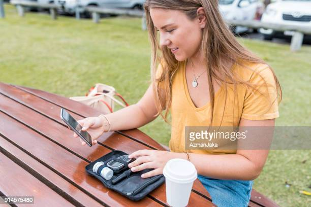 Young woman checking her blood glucose and using smart phone