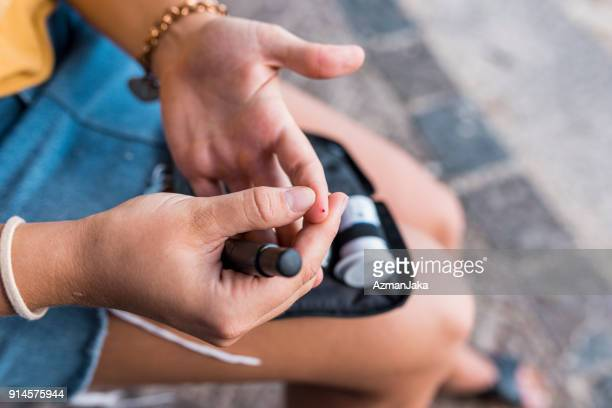 young woman checking her blood glucose - chronic illness stock photos and pictures