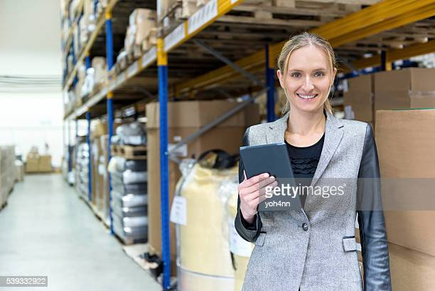 Young woman checking her deliveries in warehouse
