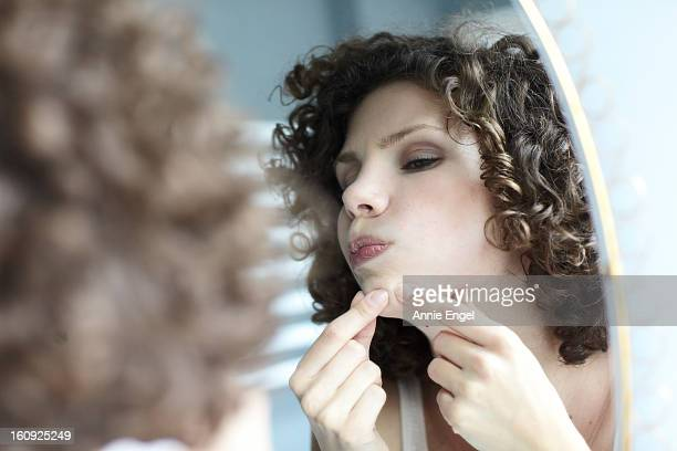 young woman checking her face in the mirror