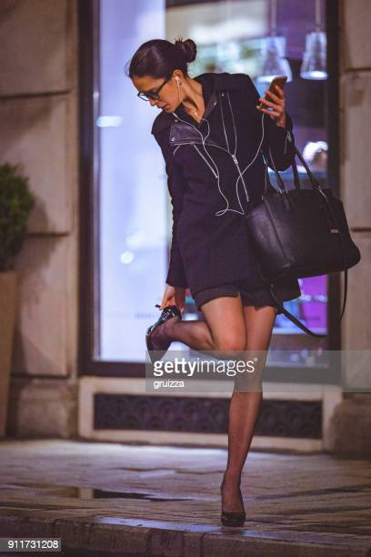 young woman checking her high heel on the city street at night - standing on one leg stock pictures, royalty-free photos & images