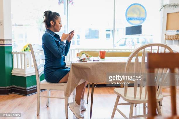 young woman checking her phone in cafe - mini dress stock pictures, royalty-free photos & images