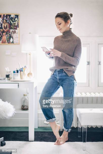 Young woman checking her phone in home office