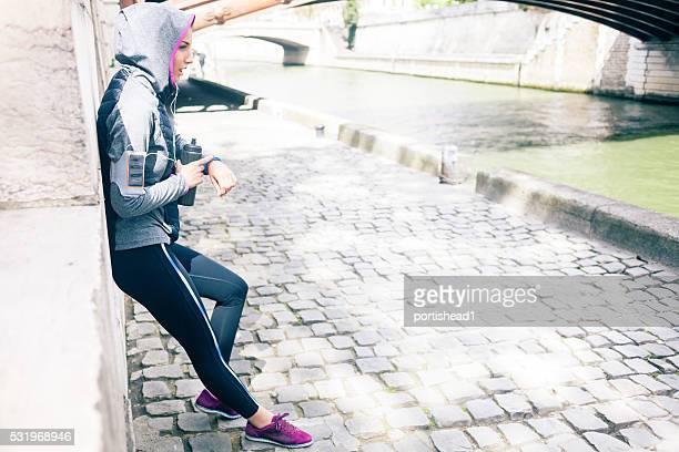 Jeune femme vérifiant son pouls après piste de faire du jogging